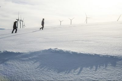 Two People Walking In The Snow With Wind Turbines